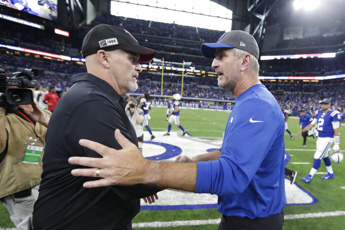Indianapolis Colts head coach Frank Reich, right, shakes hands with Atlanta Falcons head coach Dan Quinn following an NFL football game, Sunday, Sept. 22, 2019, in Indianapolis. Indianapolis won 27-24. (AP Photo/Michael Conroy)