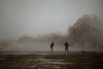 A couple take photographs of the Mediterranean sea as the waves hit the breakwater during a storm in Barcelona, Spain, Tuesday, Jan. 21, 2020. A winter storm lashed much of Spain for a third day Tuesday, leaving 200,000 people without electricity, schools closed and roads blocked by snow as it killed four people. Massive waves and gale-force winds smashed into seafront towns, damaging many shops and restaurants. (AP Photo/Emilio Morenatti)