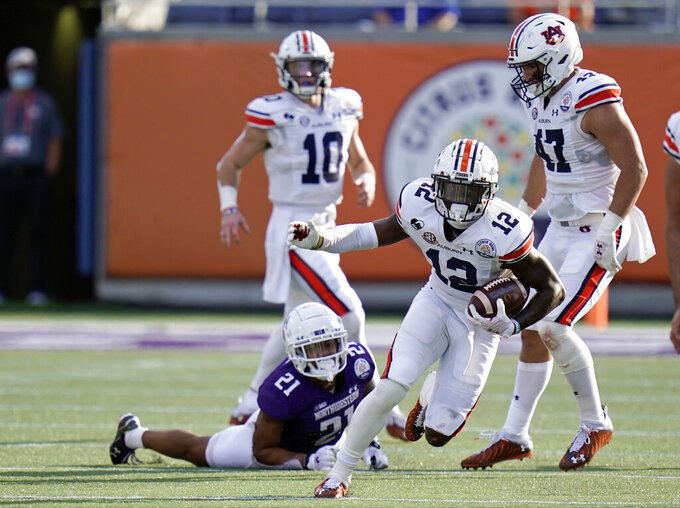 Auburn wide receiver Eli Stove (12) slips past Northwestern defensive back Cameron Mitchell (21) after a reception during the second half of the Citrus Bowl NCAA college football game, Friday, Jan. 1, 2021, in Orlando, Fla. ç (AP Photo/John Raoux)