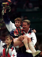 FILE - In this July 23, 1996, file photo, U.S. gymnastics coach Bela Karolyi carries injured Kerri Strug following the awarding ceremony at the women's team gymnastics competition at the Centennial Summer Olympic Games in Atlanta. The U.S. won the gold. At left is Dominique Moceanu. (AP Photo/Susan Ragan, File)