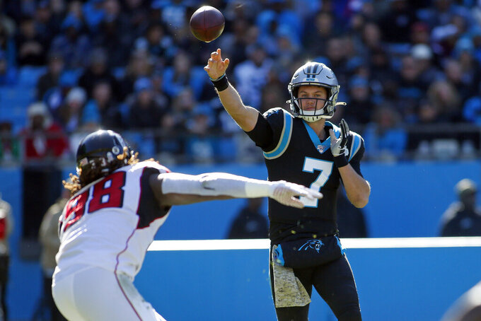 Carolina Panthers quarterback Kyle Allen (7) passes while Atlanta Falcons defensive end Takkarist McKinley (98) defends during the first half of an NFL football game in Charlotte, N.C., Sunday, Nov. 17, 2019. (AP Photo/Brian Blanco)