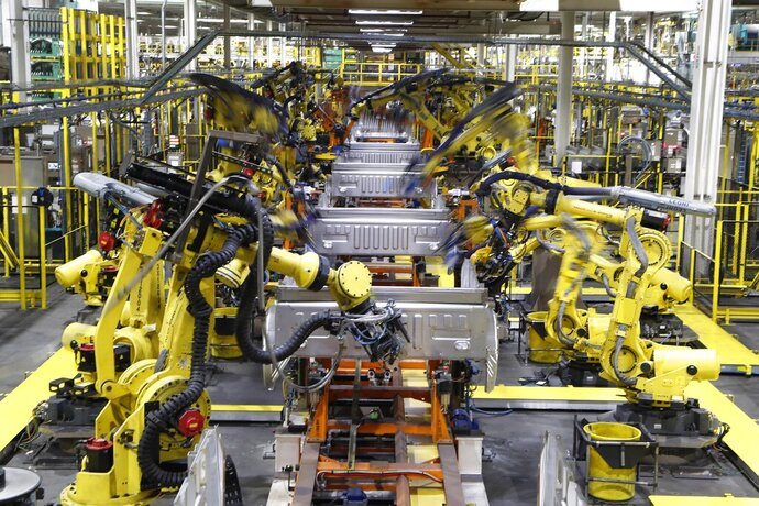FILE - In this Sept. 27, 2018, file photo robots weld the bed of a 2018 Ford F-150 truck on the assembly line at the Ford Rouge assembly plant in Dearborn, Mich. Ford says it wants to reopen five North American assembly plants in April 2020 that were closed due to the threat of coronavirus. The three Detroit automakers suspended production at North American factories March 19 ago under pressure from the United Auto Workers union, which had concerns about members working closely at work stations and possibly spreading the virus.  (AP Photo/Carlos Osorio, File)