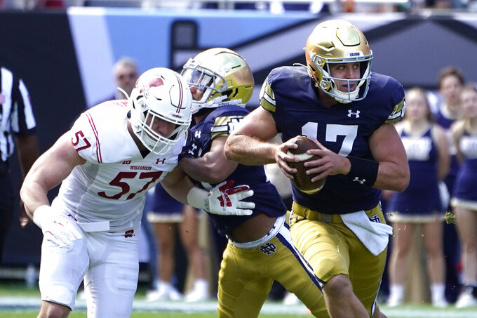 Notre Dame quarterback Jack Coan, right, scrambles away from pressure by Wisconsin linebacker Jack Sanborn during the first half of an NCAA college football game Saturday, Sept. 25, 2021, in Chicago. (AP Photo/Charles Rex Arbogast)
