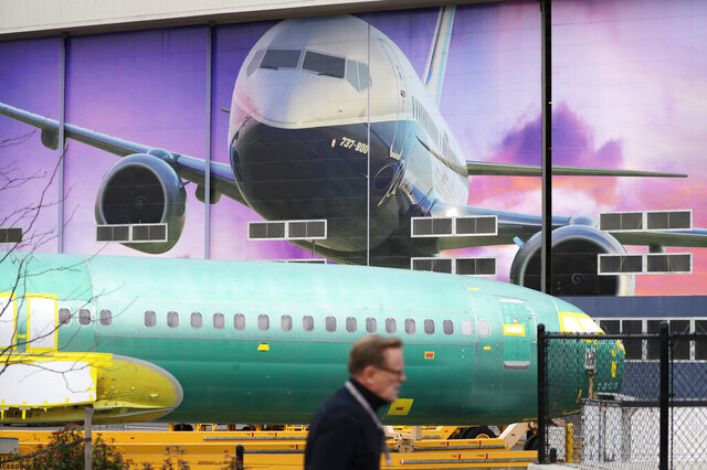 FILE - In this Dec. 16, 2019, file photo a Boeing worker walks past a 737 model fuselage and a giant mural of a jet on the side of the manufacturing building behind in Renton, Wash. On Friday, Feb. 14, 2020, the Federal Reserve reports on U.S. industrial production for January. (AP Photo/Elaine Thompson, File)