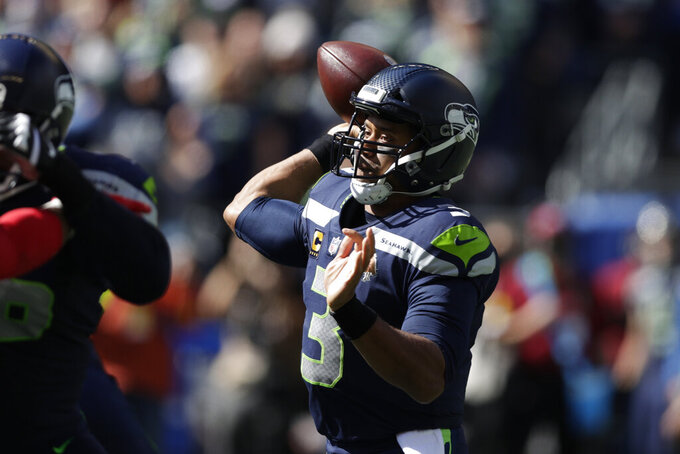 Seattle Seahawks quarterback Russell Wilson passes against the Tennessee Titans during the first half of an NFL football game, Sunday, Sept. 19, 2021, in Seattle. (AP Photo/John Froschauer)