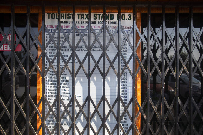 A taxi stand, which is never closed on normal days, is seen shut near the Dal lake in Srinagar, Indian controlled Kashmir,Tuesday, July 28, 2020. Indian-controlled Kashmir's economy is yet to recover from a colossal loss a year after New Delhi scrapped the disputed region's autonomous status and divided it into two federally governed territories. (AP Photo/Mukhtar Khan)