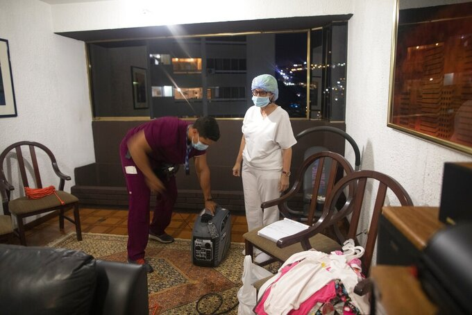 Alberto Alfonso turns on a generator to keep oxygen concentrators working as nurse Marlene Cabezasstand stands next to him in the living room of the Lares family apartment in Caracas, Venezuela, Thursday, March 18, 2021. The Lares family is being treated at home for COVID-19. (AP Photo/Ariana Cubillos)