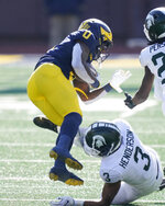 Michigan wide receiver Giles Jackson (0) is tackled by Michigan State safety Xavier Henderson (3) during the first half of an NCAA college football game, Saturday, Oct. 31, 2020, in Ann Arbor, Mich. (AP Photo/Carlos Osorio)