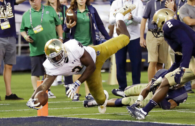 Notre Dame running back Dexter Williams leaps into the end zone for a touchdown during the first half of an NCAA college football game against Navy, Saturday, Oct. 27, 2018, in San Diego. (AP Photo/Gregory Bull)