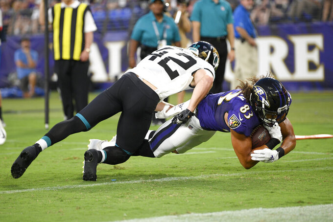 Baltimore Ravens wide receiver Willie Snead (83) dives in for a touchdown on pass from quarterback Lamar Jackson as Jacksonville Jaguars defensive back Andrew Wingard (42) tries to stop him during the first half of an NFL football preseason game Thursday, Aug. 8, 2019, in Baltimore. (AP Photo/Nick Wass)