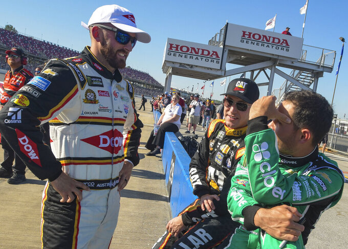 NASCAR Cup Series driver Austin Dillon, left, talks with fellow drivers Daniel Hemric, center, and Kyle Larson before qualifying for a NASCAR Cup Series auto race at Talladega Superspeedway, Saturday, April 27, 2019, in Talladega, Ala. (AP Photo/Julie Bennett)