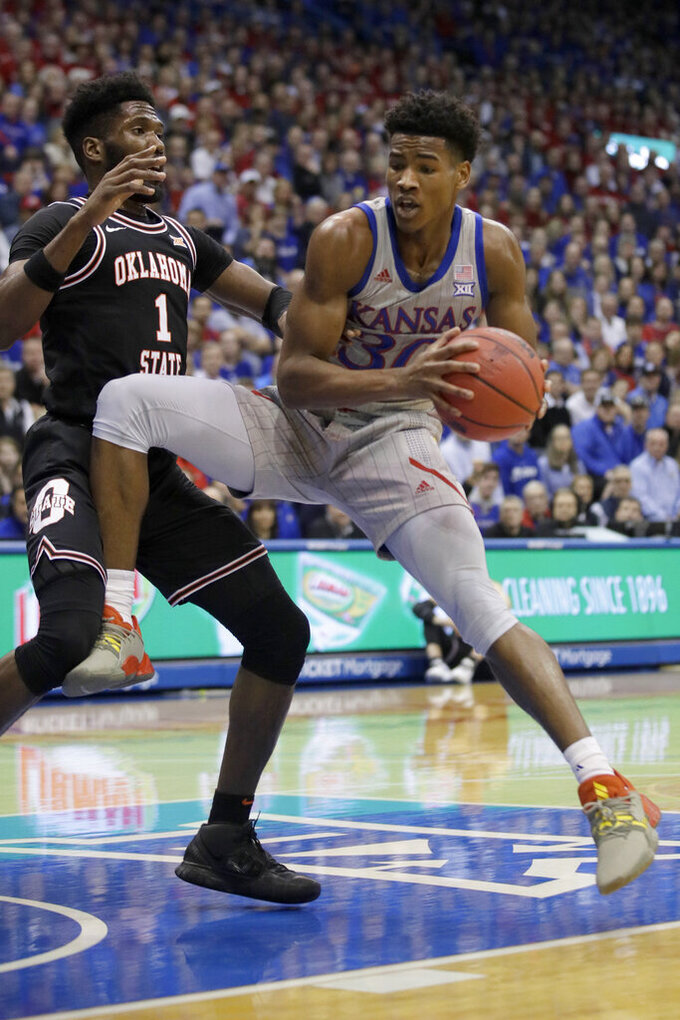 Kansas guard Ochai Agbaji (30) drives against Oklahoma State guard Jonathan Laurent (1) during the first half of an NCAA college basketball game in Lawrence, Kan., Monday, Feb. 24, 2020. (AP Photo/Orlin Wagner)