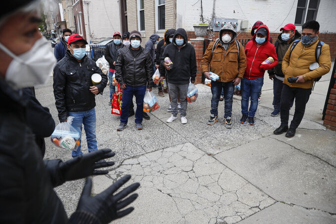 Fabian Arias, left, a Lutheran pastor with Saint Peter's Church in Manhattan, speaks to men who gathered to receive his food donations on a sidewalk, about the importance of social distancing, Friday, May 8, 2020, in the Brooklyn borough of New York. (AP Photo/John Minchillo)