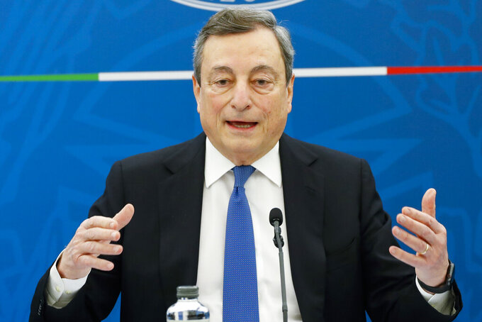 """Italian Premier Mario Draghi gestures as he addresses the media during a news conference, in Rome, Friday, April 16, 2021. Draghi announced Friday that Italy will take a """"reasoned risk"""" in reopening restaurants with outdoor seating and school at all grade levels in some regions from April 26. The openings will apply to regions that have the lowest tiers of restrictions and require both mask-wearing and social distancing be """"scrupulously observed."""" (Remo Casilli/Pool via AP)"""