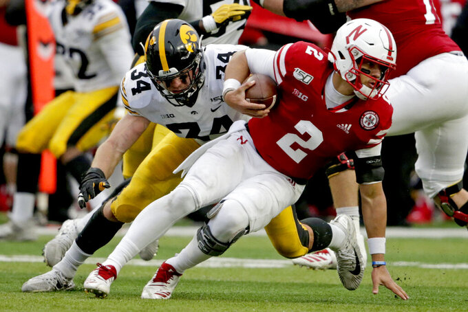 Nebraska quarterback Adrian Martinez (2) breaks a tackle by Iowa linebacker Kristian Welch (34) during the first half of an NCAA college football game in Lincoln, Neb., Friday, Nov. 29, 2019. (AP Photo/Nati Harnik)