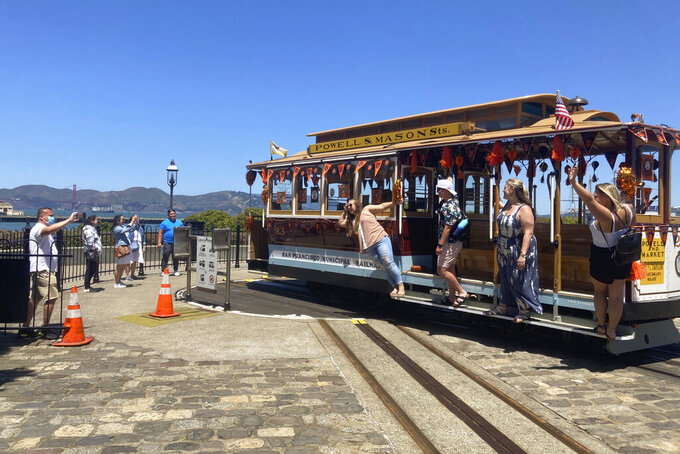 People pose for pictures on a cable car at the Hyde Street cable car turnaround in San Francisco on Tuesday, June 15, 2021. The mayor announced Tuesday that the famed cable cars would be running again in August after being halted at the start of the pandemic. (AP Photo/Olga Rodriguez)