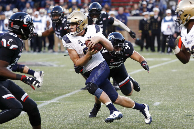 Navy wide receiver Zach Abey, center left, is tackled by Cincinnati linebacker Kyle Bolden (34) in the second half of an NCAA college football game, Saturday, Nov. 3, 2018, in Cincinnati. (AP Photo/John Minchillo)