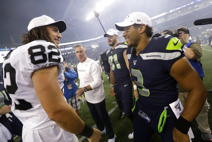 Seattle Seahawks quarterback Russell Wilson, right greets a former teammates, Oakland Raiders tight end Luke Willson (82), after an NFL football preseason game Thursday, Aug. 29, 2019, in Seattle. The Seahawks won 17-15. (AP Photo/Elaine Thompson)