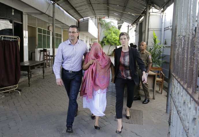 FILE- In this Monday, Dec. 30, 2019 file photo, a Swiss Embassy employee who was detained pending charges that she made statements to create disaffection toward the government and fabricated evidence, center, walks out with two unidentified embassy employees after getting bail in Colombo, Sri Lanka. The Swiss embassy in Sri Lanka  has recalled that the safety of diplomatic missions is a responsibility of the host state, days after a local Swiss embassy staffer detained for two weeks for allegedly causing disaffection toward the government was released on bail. (AP Photo/Eranga Jayawardena, File)