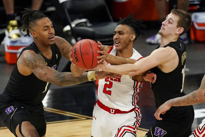 Washington's Nate Roberts, left, and Erik Stevenson, right, attempt to get the ball from Utah's Ian Martinez (2) during the second half of an NCAA college basketball game in the first round of the Pac-12 men's tournament Wednesday, March 10, 2021, in Las Vegas. (AP Photo/John Locher)