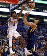 Phoenix Suns forward Kelly Oubre Jr. (3) dunks over Utah Jazz center Rudy Gobert during the second half of an NBA basketball game, Monday, Oct. 28, 2019, in Phoenix. The Jazz won 96-95. (AP Photo/Matt York)