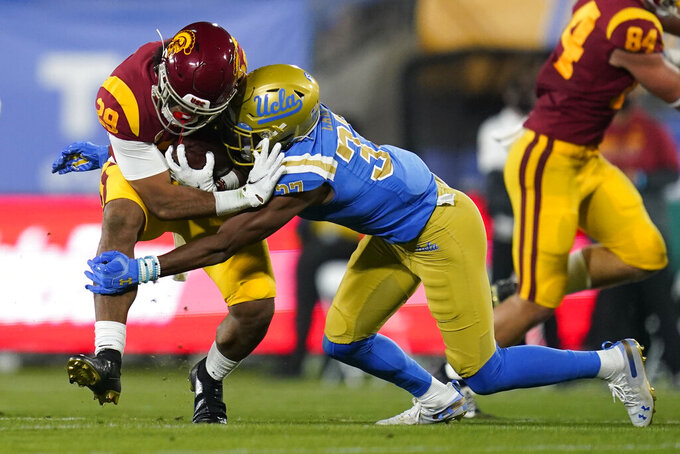 Southern California running back Vavae Malepeai, left, is tackled by UCLA defensive back Quentin Lake (37) during the second quarter of an NCAA college football game Saturday, Dec 12, 2020, in Pasadena, Calif. (AP Photo/Ashley Landis)