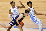 Notre Dame guard Cormac Ryan (5) grabs the ball as North Carolina forward Armando Bacot (5) and teammate guard Kerwin Walton (24) defend during the first half of an NCAA college basketball game in the second round of the Atlantic Coast Conference tournament in Greensboro, N.C., Wednesday, March 10, 2021. (AP Photo/Gerry Broome)