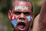 A Papuan activist with his face painted with the colors of the separatist Morning Star flag shouts slogans during a rally near the presidential palace in Jakarta, Indonesia, Thursday, Aug. 22, 2019. A group of West Papuan students in Indonesia's capital staged the protest against racism and called for independence for their region. (AP Photo/Dita Alangkara)