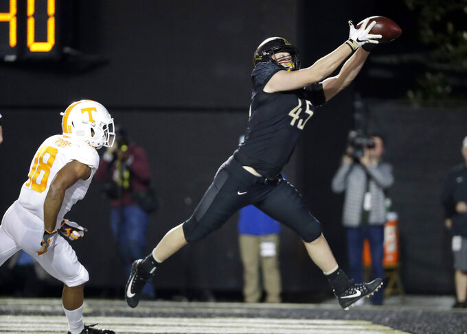 Vanderbilt tight end Cody Markel (45) catches a 2-yard touchdown pass ahead of Tennessee defensive back Nigel Warrior (18) in the second half of an NCAA college football game Saturday, Nov. 24, 2018, in Nashville, Tenn. (AP Photo/Mark Humphrey)