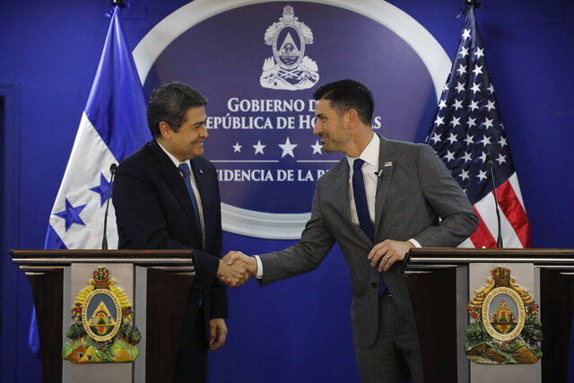 Acting Secretary of Homeland Security Chad F. Wolf, right, shakes hands with Hondura's President Juan Orlado Hernandez during a press conference in Tegucigalpa, Honduras, Thursday, Jan. 9, 2020. Wolf said that the two countries had finalized their implementation of an agreement that would send third country asylum seekers from the U.S. to Honduras. (AP Photo/Elmer Martinez)