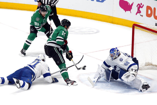 Dallas Stars left wing Jamie Benn, center, skates past Tampa Bay Lightning center Brayden Point, left, and shoots the game winning goal past goaltender Andrei Vasilevskiy, right, during overtime of an NHL hockey game in Dallas, Monday, Jan. 27, 2020. (AP Photo/Ray Carlin)