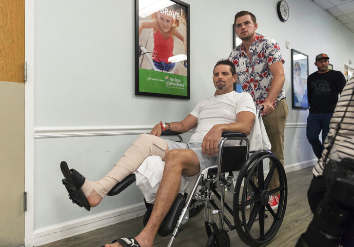 In this Nov. 12, 2019 photo, Corey Boyce pushes his father James Boyce to a press conference at St. Mary's Medical Center in West Palm Beach, Fla. Boyce was bitten on his right leg by an alligator while hunting in Martin County, Fla.  Nearby hunters and a rescue crew teamed up to save his life. (Greg Lovett/Palm Beach Post via AP)