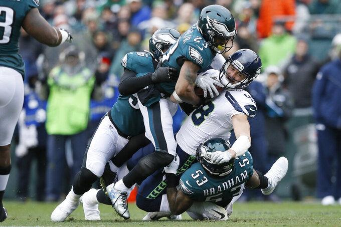 Seattle Seahawks' Jacob Hollister (48) is tackled by Philadelphia Eagles' Nigel Bradham (53), Rodney McLeod (23) and Derek Barnett (96) during the first half of an NFL football game, Sunday, Nov. 24, 2019, in Philadelphia. (AP Photo/Michael Perez)