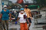 People wear face masks as they walk outside the Dala jetty in Yangon, Myanmar Tuesday, July 27, 2021. (AP Photo)