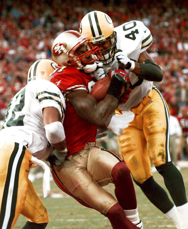 FILE - In this Jan. 3, 1999, file photo, San Francisco 49ers' wide receiver Terrell Owens pulls in a 25-yard touchdown pass from quarterback Steve Young as Green Bay Packers' safeties Pat Terrell (40) and Darren Sharper defend late in the fourth quarter of an NFC wild card playoff game at 3COM Park in San Francisco. Owens' catch with three seconds left in the game led the 49ers to a 30-27 win. The two teams that have combined for nine Super Bowl titles will meet with a spot in the ultimate game on the line once again when the 49ers (14-3) host the Packers (14-3) in the NFC championship game on Sunday, Jan. 19, 2020. (AP Photo/Susan Ragan, File)