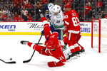 Detroit Red Wings defenseman Dennis Cholowski (21) is dumped by Vancouver Canucks center Tim Schaller (59) during the third period of an NHL hockey game Tuesday, Oct. 22, 2019, in Detroit. (AP Photo/Paul Sancya)