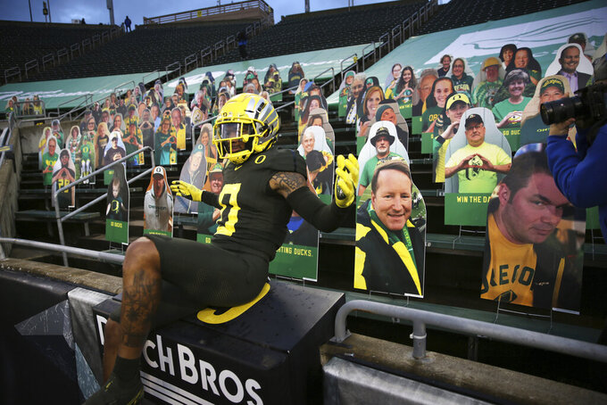 FILE - In this Nov. 7, 2020, file photo, Oregon's Deommodore Lenoir jumps onto a stands filled with fan cutouts to take the place of the fans not allowed in the stadium before the Stanford-Oregon NCAA college football game in Eugene, Ore. (AP Photo/Chris Pietsch, File)