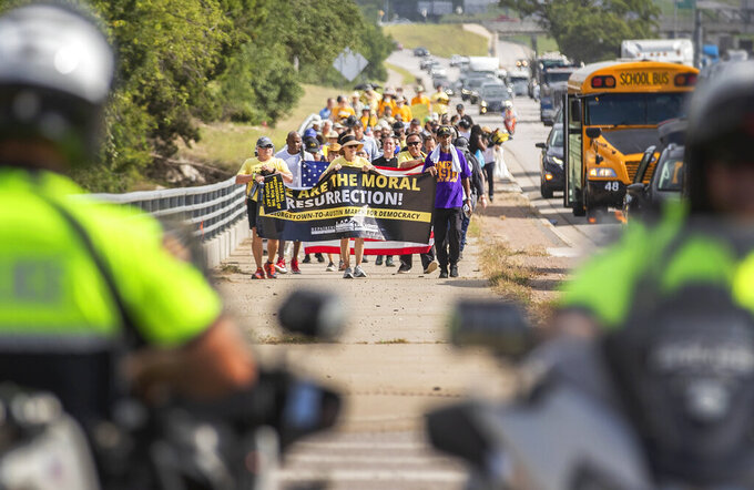 A group of people make a stop at Good Hope Church in Round Rock, Texas, Wednesday, July 28, 2021 during a march from Georgetown, Texas to the Texas State Capitol in downtown Austin. Church leaders and former Democratic congressman Beto O'Rourke are leading the nearly 30-mile voting rights march in Texas. The walk began with nearly 100 participants in suburban Austin and will is scheduled to end this weekend at the state Capitol. The march is the latest effort by Democrats to keep up the pressure over voting rights at a time when the prospects of action from Congress is fading. (Ricardo B. Brazziell/Austin American-Statesman via AP)