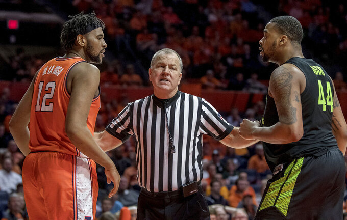 An official gets between Illinois center Adonis De La Rosa (12) and Michigan State forward Nick Ward (44) during the second half of an NCAA college basketball game in Champaign, Ill., Tuesday, Feb. 5, 2019. Illinois won 79-74. (AP Photo/Rick Danzl)