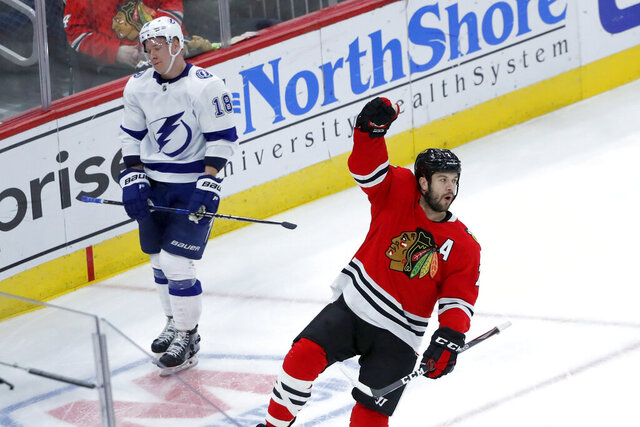Chicago Blackhawks' Brent Seabrook, right, celebrates his goal as Tampa Bay Lightning's Ondrej Palat skates by during the third period of an NHL hockey game Thursday, Nov. 21, 2019, in Chicago. Tampa Bay won 4-2. (AP Photo/Charles Rex Arbogast)