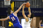 UMass-Lowell forward Joey Glynn, left, blocks a shot-attempt of Michigan guard Adrien Nunez during the first half of an NCAA college basketball game, Sunday, Dec. 29, 2019, in Ann Arbor, Mich. (AP Photo/Jose Juarez)