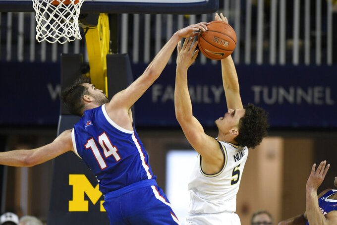 UMass-Lowell forward Joey Glynn, left, blocks a shot-attempt of Michigan guard Adrien Nunez during the first half of an NCAA college basketball game, Sunday, Dec. 29, 2019, in Ann Arbor, Mich. (AP Photo/Jose Juarez)