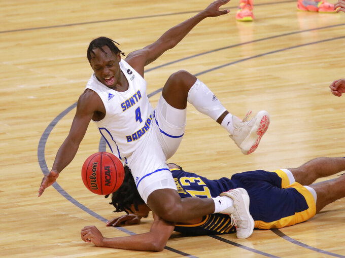 UC Santa Barbara's Devearl Ramsey (4) scrambles over UC Irvine's Austin Johnson (13) for a loose ball during the first half of an NCAA college basketball game for the championship of the Big West Conference men's tournament Saturday, March 13, 2021, in Las Vegas. UC Santa Barbara won 79 to 63. (AP Photo/Ronda Churchill)
