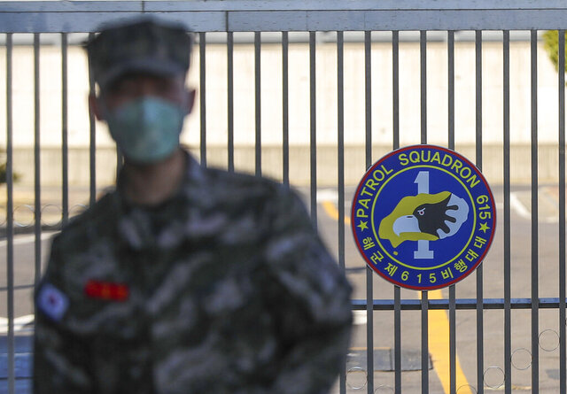 In this Feb. 21, 2020, photo, a South Korean marine wearing a mask stands in front of the Navy Base after a soldier of the unit was confirmed to have been infected with the coronavirus on Jeju Island, South Korea. The U.S. and South Korean militaries, used to being on guard for threats from North Korea, face a new and formidable enemy that could hurt battle readiness: a virus spreading around the world that has infected more than 1,200 people in South Korea. (Woo Jang-ho/Yonhap via AP)