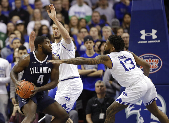 Seton Hall guard Myles Powell (13) and forward Sandro Mamukelashvili, center, defend as Villanova forward Eric Paschall (4) looks to make a move during the second half of an NCAA college basketball game, Saturday, March 9, 2019, in Newark, N.J. Seton Hall defeated Villanova 79-75. (AP Photo/Kathy Willens)