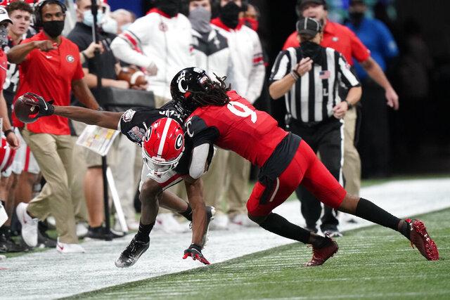 Georgia wide receiver George Pickens (1) is hit by Cincinnati cornerback Arquon Bush (9) during the second half of the Peach Bowl NCAA college football game, Friday, Jan. 1, 2021, in Atlanta. (AP Photo/Brynn Anderson)