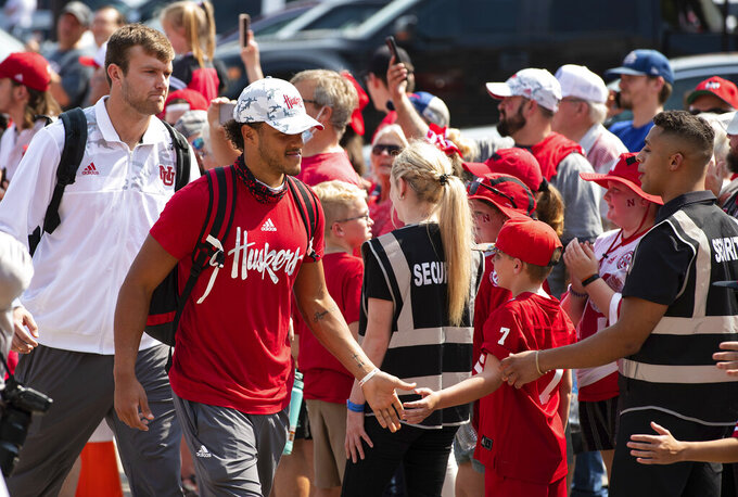 Nebraska quarterback Adrian Martinez, second left, is greeted by fans during the unity walk as the Husker team arrives before playing against Buffalo in an NCAA college football game, Saturday, Sept. 11, 2021, at Memorial Stadium in Lincoln, Neb. (AP Photo/Rebecca S. Gratz)