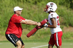 In this photo taken Thursday, Aug. 9, 2018 North Carolina State coach Dave Doeren, left, runs a drill with cornerback Taiyon Palmer during an NCAA college football practice in Raleigh, N.C. (AP Photo/Gerry Broome)