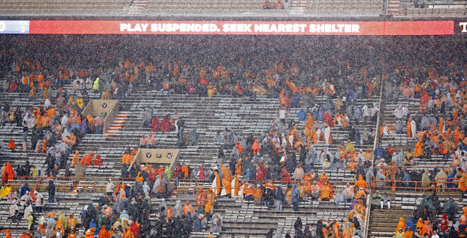 Fans head for shelter as lightning was detected in the area before an NCAA college football game between Tennessee and Vanderbilt Saturday, Nov. 30, 2019, in Knoxville, Tenn. (AP Photo/Wade Payne)