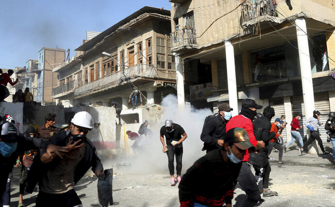 Riot police fire tear gas while blocking al-Rashid Street during clashes with anti-government demonstrators in Baghdad, Iraq, Friday, Nov. 22, 2019. Iraq's massive anti-government protest movement erupted Oct. 1 and quickly escalated into calls to sweep aside Iraq's sectarian system. Protesters occupy several Baghdad squares and parts of three bridges in a standoff with security forces. (AP Photo/Hadi Mizban)
